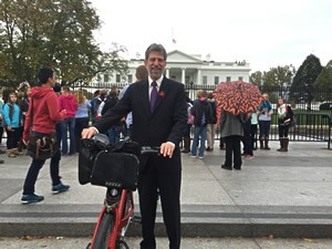 Tim Young stands before the White House in DC with his bike-share bike.